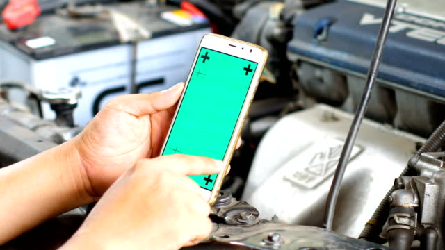 Technician Using Smart Phone with Green Screen for Diagnostic Car, Car Maintenance Concept