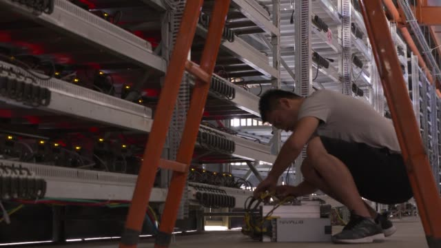 A technician walks past bitcoin mining machines at a mining facility operated by Bitmain Technologies Ltd in Ordos Inner Mongolia China on Friday Aug...