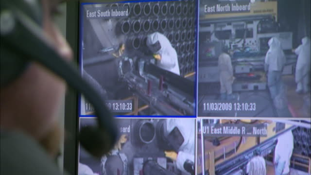 A technician watches a computer screen showing four security camera's images.
