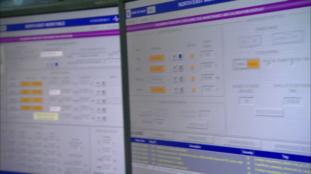 A technician watches two computer screens and a security monitor at a work table.