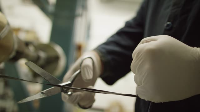 a technician wearing protective gloves uses a pair of metal scissors to cut a string of black carbon fiber in an indoor manufacturing facility - string stock videos & royalty-free footage