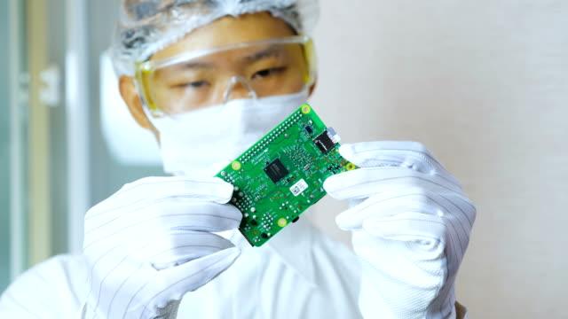 マイクロ コンピューター基板を持つ技術者 - クリーンスーツ点の映像素材/bロール