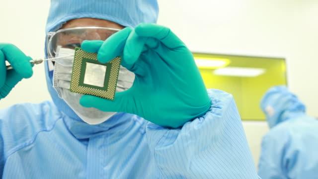 Techniker mit Mikrochip im Reinraum Labor