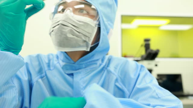 研究室のクリーン ルームにはマイクロ チップを持つ技術者 - 半導体点の映像素材/bロール