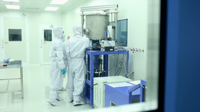 technician with microchip in the lab clean room - clean room stock videos and b-roll footage