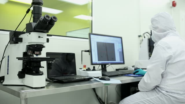 technician with microscope, in the lab clean room - clean room stock videos and b-roll footage