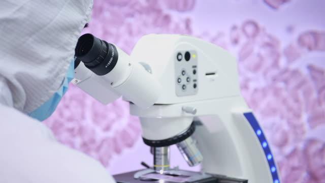 Techniker mit Mikroskop, im Reinraum Labor