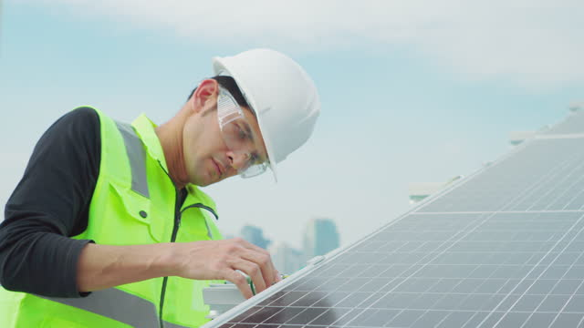 technician worker installing and working on maintenance of solar photovoltaic panel installed. - sports helmet stock videos & royalty-free footage