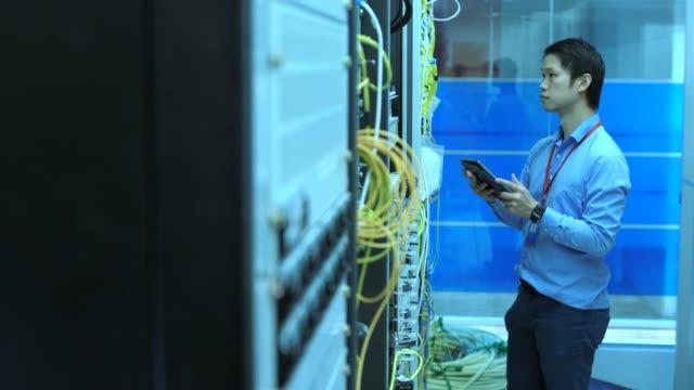 vídeos y material grabado en eventos de stock de técnico trabaja en sala de servidores - 30 39 years