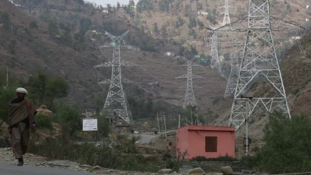 a technician works on a sterlite power transmission ltd transmission tower in rajouri district jammu and kashmir india on thursday nov 16 a man walks... - south asia stock videos and b-roll footage