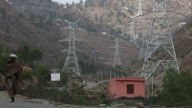 A technician works on a Sterlite Power Transmission Ltd transmission tower in Rajouri district Jammu and Kashmir India on Thursday Nov 16 A man walks...