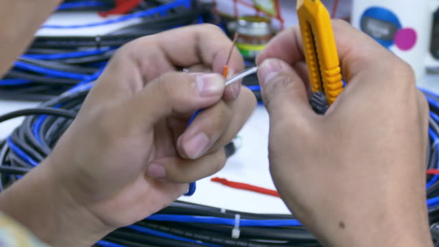 Technicians are stripping wires on isolated