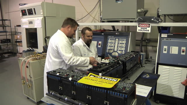CU ZO Technicians confer while testing prototype lithium ion battery used to power electric automobile / Troy, Michigan, USA