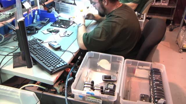 vidéos et rushes de ms tu technicians disassembling and examining cell phones in workshop / dexter, michigan, usa - entretien