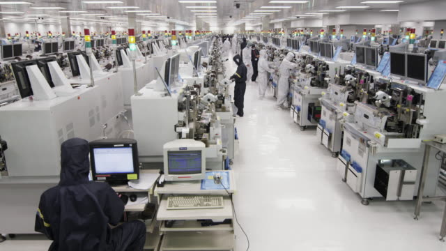 WS Technicians inspecting newly manufactured semiconductors under microscopes / Bang Pa-In, Ayutthaya, Thailand