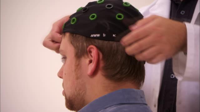 technicians prepare volunteers for brain scans. - scientific experiment stock videos & royalty-free footage