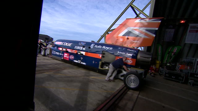 Technicians push the Bloodhound supersonic car back into an aircraft hanger
