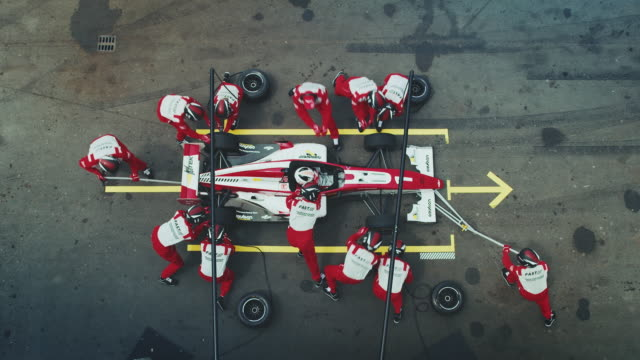 technicians repairing formula one car at pit stop - road marking stock videos & royalty-free footage