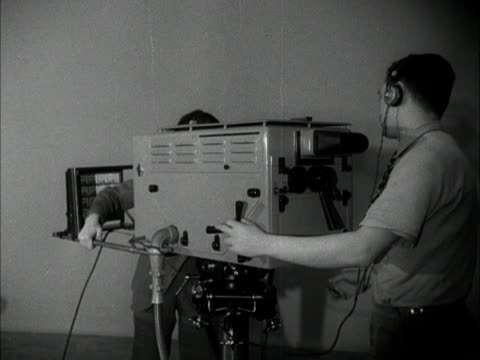 vídeos y material grabado en eventos de stock de technicians set up and check a camera in the new bbc children's hour studio at lime grove. - cámara de televisión