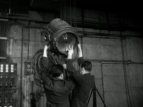Technicians set up studio lights in the new BBC Children's Hour studio at Lime Grove 1950