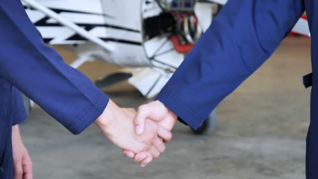 technicians shake hands in the hangar - airplane hangar stock videos & royalty-free footage