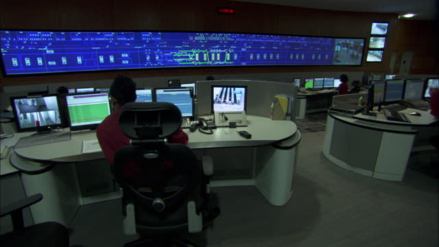 Technicians work at multiple workstations with computers and a large surveillance monitor.