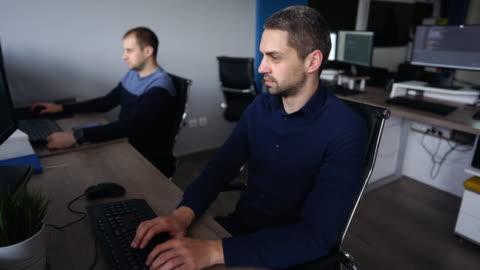 it-techniker arbeiten im büro - code stock-videos und b-roll-filmmaterial
