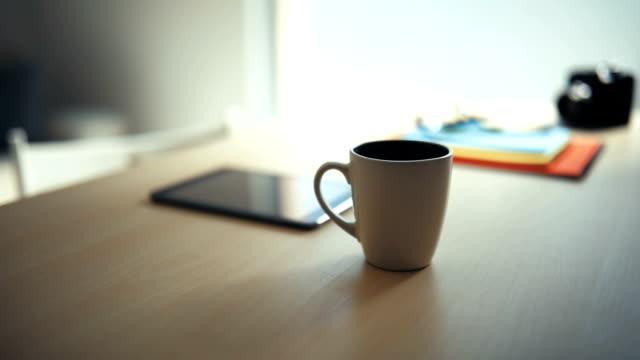 Technologie und Kaffee auf einem Holztisch.