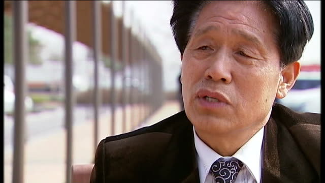 technology helps outside world seep into north korea south reporter listening jo gyeong sang interview sot wide shot of buildings in north korea... - 2013年 北朝鮮の核実験点の映像素材/bロール