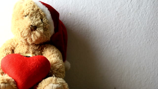 Teddy bear holding head in red on a gray wall background.