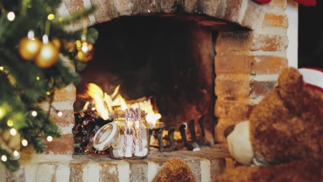 4K Teddy bear in Santa hat by cozy Christmas fireplace, real time