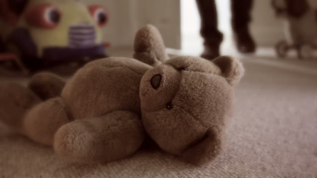 Teddy bear on bedroom floor.