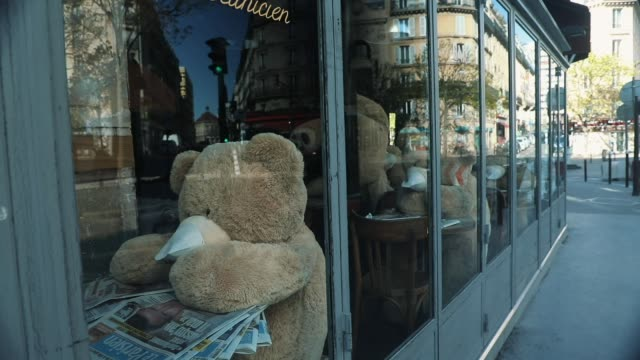 teddy bears wearing masks are seen displayed at the 'la manufacture' cafe in the 'les gobelins' area on april 15, 2020 in paris, france. the bears,... - テディベア点の映像素材/bロール