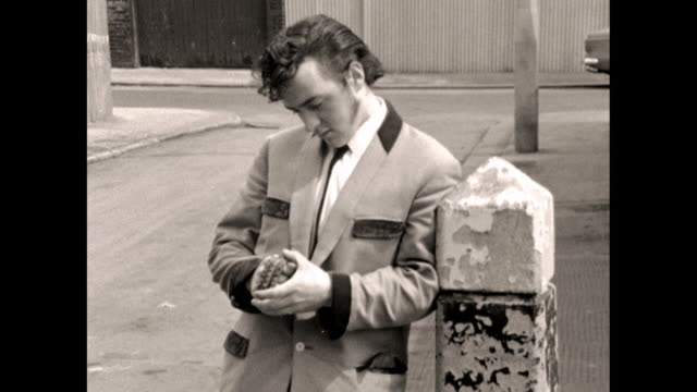 teddy boy leans against a fence post with knuckledusters - one teenage boy only stock videos & royalty-free footage