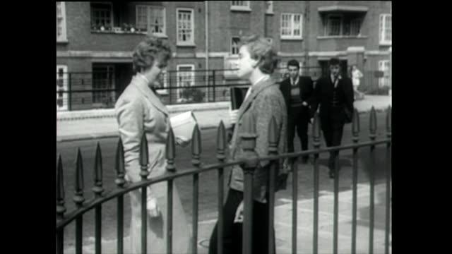 vídeos de stock, filmes e b-roll de teddy boys meet girlfriends on street; 1955 - de braços dados