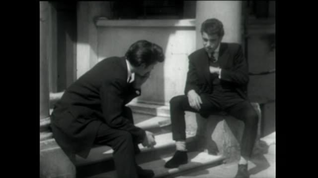 teddy boys sit on doorstep talking and combing hair; 1955 - teddy boy stock videos & royalty-free footage