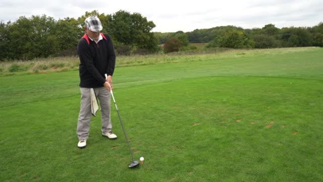 vídeos de stock, filmes e b-roll de teeing off as the camera pans round from side to back. - bolsa de golfe