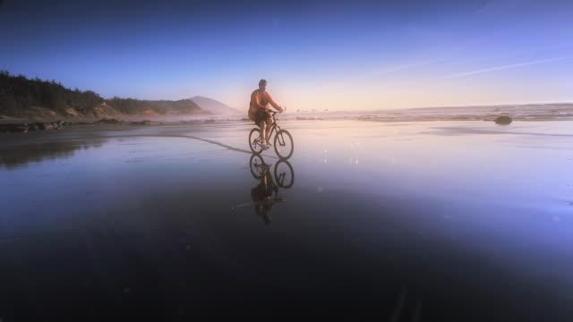 Teen age boy riding mountain bike on ocean beach at sunset