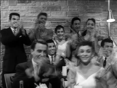 B/W 1956 teen audience in semi-formal attire enthusiastically applauding someone offscreen