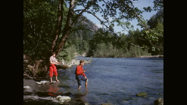 WS Teen boy and girl fishing in river / United States