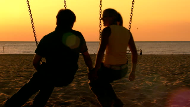 vidéos et rushes de teen boy and girl sitting on swings at the beach holding hands as the sun goes down - couple d'adolescents