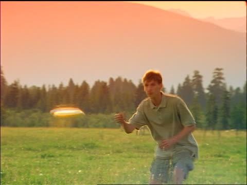 stockvideo's en b-roll-footage met filter teen boy catching a plastic disc in field / montana - alleen één tienerjongen