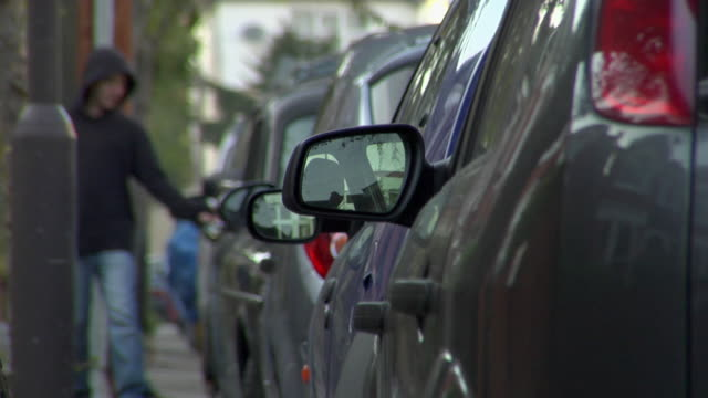 vidéos et rushes de cu teen boy checking door locks on row of parked cars / london, england - stationary