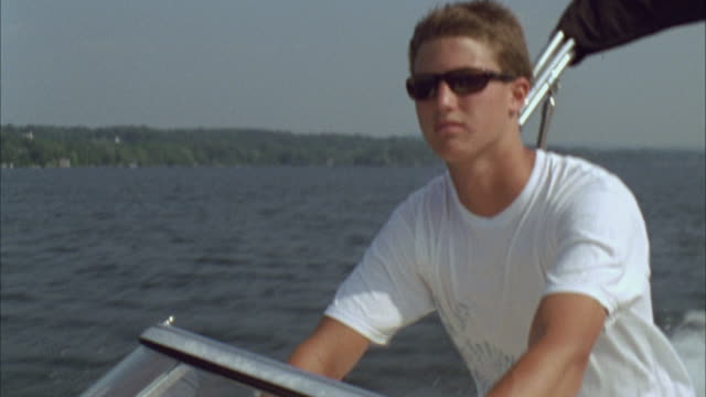 MS TU Teen boy driving motorboat across lake / Cazenovia, New York, USA