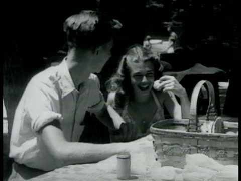 dramatization teen boy girl sitting outdoors at picnic table w/ food basket talking laughing young adult male female couples on beach talking... - picnic basket stock videos and b-roll footage