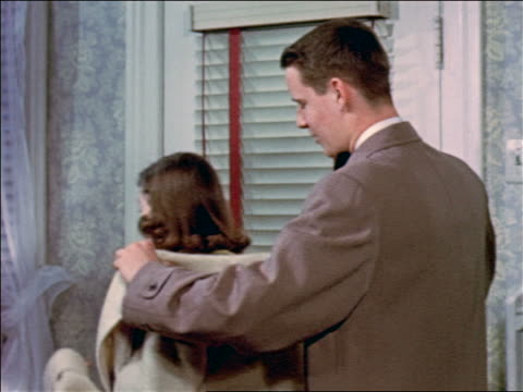1953 teen boy helping girl put on coat then opening door for her / educational - high society stock videos & royalty-free footage