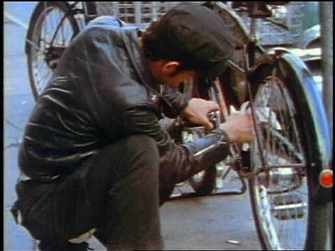 1957 teen boy in leather jacket wiping bicycle outdoors / feature - 1957 stock videos & royalty-free footage