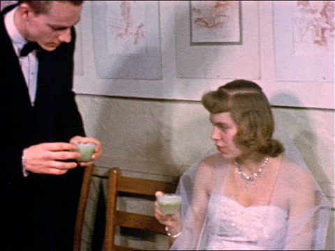 1953 teen boy in tuxedo giving cup of punch to seated girl in formal dress / educational
