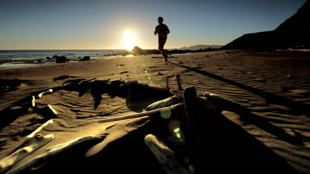 teen boy jogging on pacific beach at sunset - in silhouette stock videos & royalty-free footage