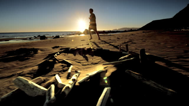 Teen boy jogging on Pacific Beach at sunset